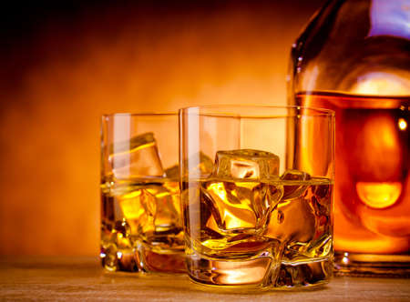 Two glasses of whiskey on the rocks and a bottle Stock Photo