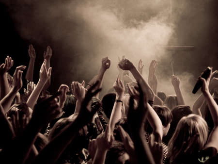 Crowd at a concert with hands up in the air