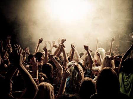 Menigte bij een concert met handen uup, hoge ISO
