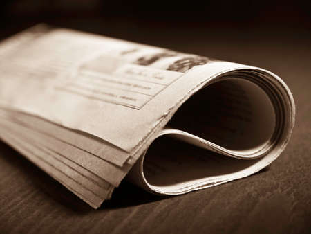 Rolled newspaper on the table Standard-Bild