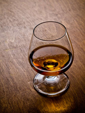 cognac: One glass of cognac on a wooden table