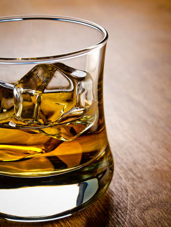 whisky: One glass of whiskey on the rocks on a wooden table
