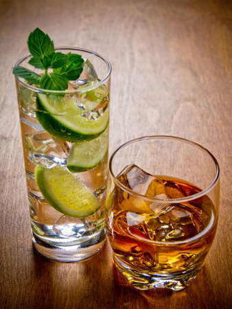 gin: Two glasses of alcohol beverages, gin and tonic and whiskey on the rocks