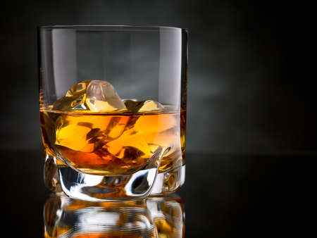 bourbon: One glass of whisky on the rocks on black background