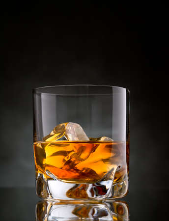 One glass of whisky on the rocks on black background
