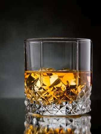 whisky glass: One glass of whisky on the rocks on black background