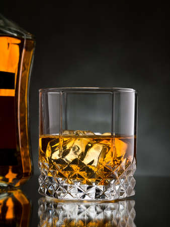 whisky glass: Glass of whisky on the rocks with a bottle Stock Photo
