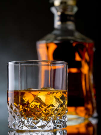 whisky bottle: Glass of whisky on the rocks with a bottle Stock Photo