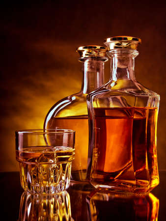 whisky bottle: Glass and a bottle of whisky against red and yellow background Stock Photo