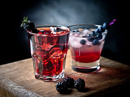 gin: Blueberry and blackberry cocktails on a wooden board