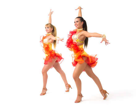 Two female salsa dancers in colorful dresses over white background