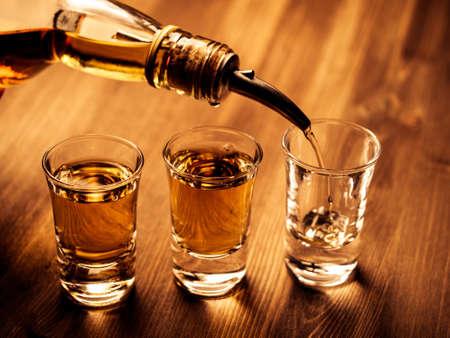 Trois verres à liqueur étant remplis avec un verre Banque d'images - 38851187