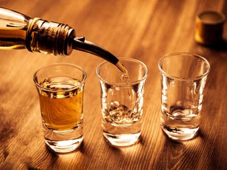 Trois verres à liqueur étant remplis avec un verre Banque d'images - 38851191