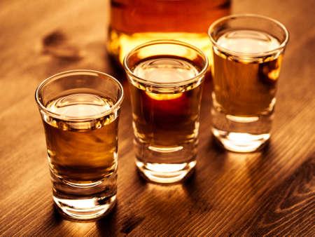 botella de whisky: Tres disparos y una botella sobre una mesa