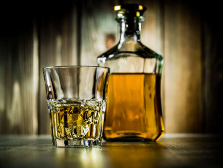 Glass of whiskey on the rocks and a bottle on a wooden background Stock Photo