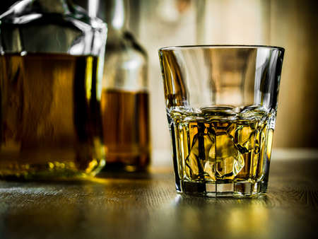 Glass of whiskey on the rocks and two bottles on a wooden background
