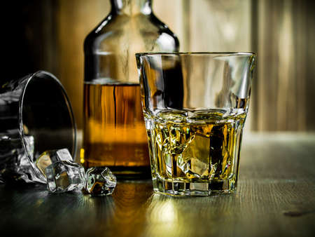 drinks on bar: Glass of whiskey on the rocks and a bottle on a wooden background Stock Photo