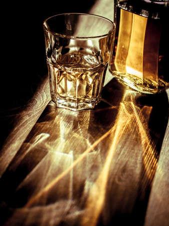 botella de whisky: Whisky en las rocas con luz de fondo y reflejos fuertes