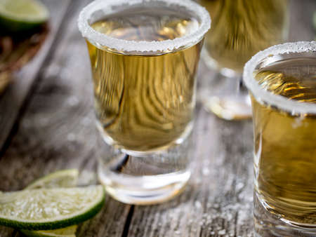 fruit of the spirit: Tequila shots served with salt rim and lime wedges on a grunge wooden table Stock Photo