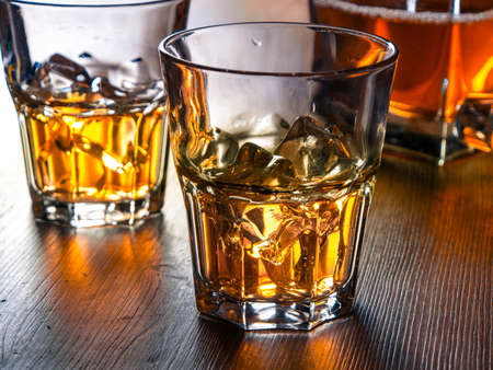 whiskey on the rocks: Two glasses of whiskey on the rocks on a wooden table