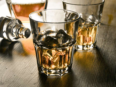 bar top: Two glasses of whiskey on the rocks on a wooden table