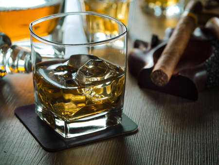 ashtray: One glass of whiskey on the rocks on a wooden table