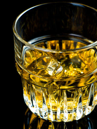whiskey on the rocks: Glass of whiskey on the rocks on black background