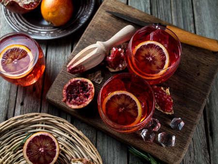 Blood orange and pomegranate cocktails on a grunge wooden table