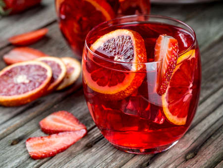 Rum punch with blood orange and strawberries on a wooden table Standard-Bild