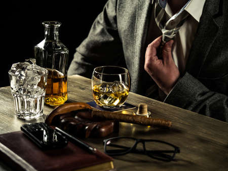 loosen: Businessman relieving stress after a hard working day drinking whiskey