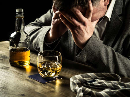 stressed out: Stressed out businessman drinking whiskey