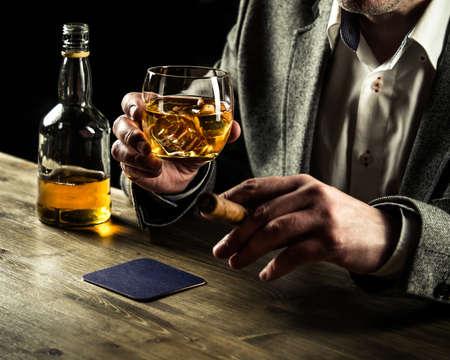 Gut gekleidete Mann mit einer Zigarre trinken Whisky Standard-Bild - 56350087