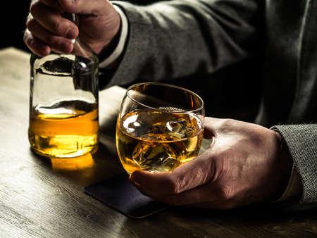 Mann trägt Jacke mit einem Glas Whisky an der Theke Standard-Bild - 56350093
