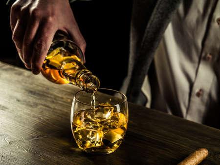 Geschäftsmann gießt Whisky in seinem Glas Standard-Bild - 56350096