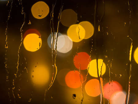pane: Raindrops and water trickling down a window pane with defocused street lights in the back Stock Photo
