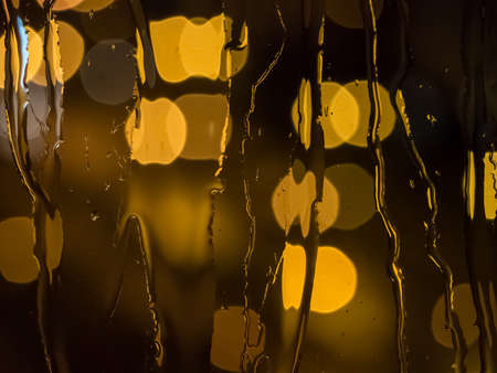 trickling: Raindrops and water trickling down a window pane with defocused street lights in the back Stock Photo