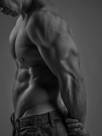 young male: Side view of a muscular young man posing shirtless