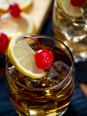 Whiskey sour cocktail garnished with lemon slice and maraschino cherry Stock Photo