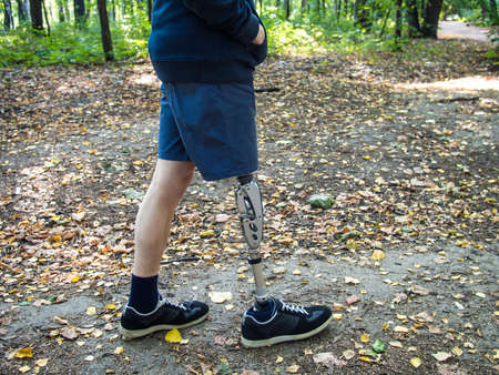 Young man with prosthetic leg walking in a park in autumn