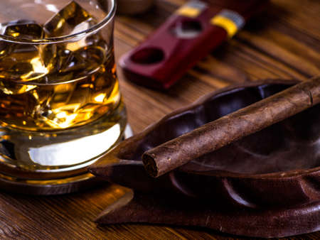 Glass of whisky on the rocks and a cigar in a wooden ashtray