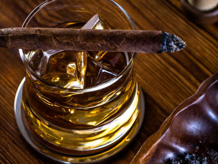 Glass of whisky on the rocks with a birning cigar on top of it