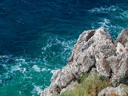 Blue and azure sea waters and rocky cliff Imagens