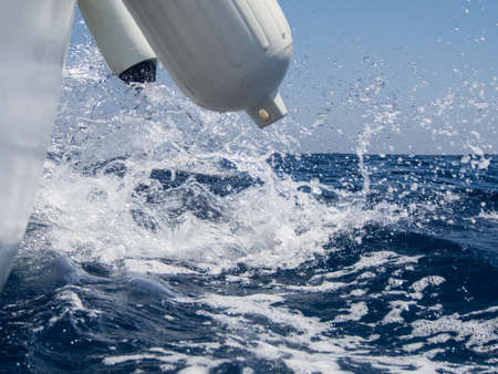 Seawater splashes at the board of a sailing boat Stock Photo
