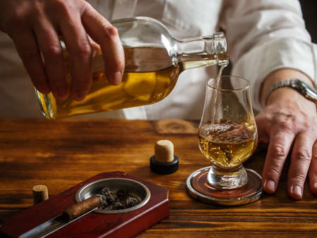 Man in white shirt pouring whisky in a glencairn glass