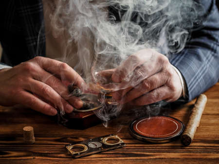 A well-dressed man at a bar drinks single malt whisky and smokes a cigar
