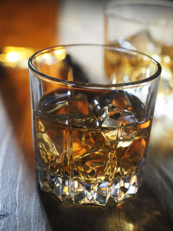 Two glasses of whisky on the rocks on a wooden table