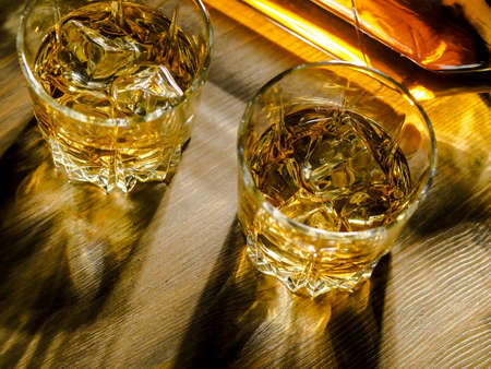 Two glasses of whisky on the rocks on a wooden table Zdjęcie Seryjne