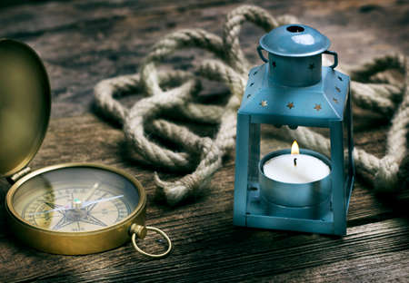 compass, rope and blue lantern with candle on grunge wooden background