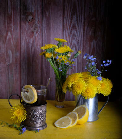 cup holder tea with lemon, sugar and dandelions flowers