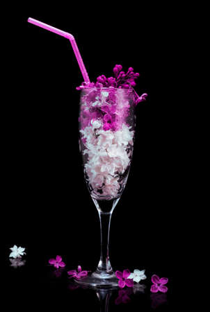 Lilac flowers in glass isolated on black background. cocktail